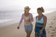 Mother and daughter walking on beach stock images