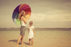 Mother and  daughter walking on the beach Stock Images