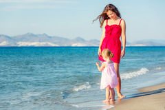 Mother and daughter walking on the beach Stock Photos