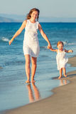 Mother and daughter walking on the beach Royalty Free Stock Image