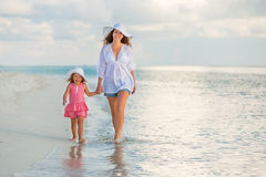 Mother and daughter walking on the beach Stock Photo