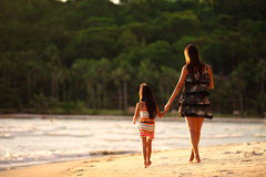 Mother and daughter walking on beach Stock Photo