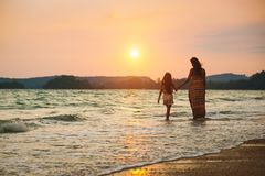 Mother and daughter walking on the beach with sunset stock photography