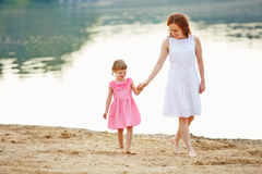 Mother and daughter walking on beach Royalty Free Stock Image