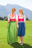 Mother and daughter walking both go hand in hand in a dirndl. Mother and daughter both in dirndl go hand in hand on a sunny day for a walk in a meadow in the royalty free stock photo