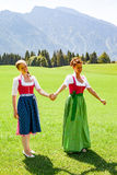 Mother and daughter walking both go hand in hand in a dirndl. Mother and daughter both in dirndl go hand in hand on a sunny day for a walk in a meadow in the stock image