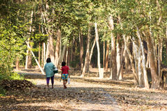Mother and daughter walking on country rural road, they are goin Royalty Free Stock Image