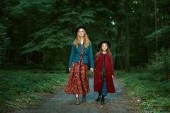 Mother and daughter are walking through the forest. Stock Photo