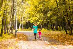 Mother and daughter walking holding hands at park. Family lifestyle, autumn season concept Royalty Free Stock Photography