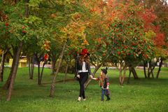 Mother and daughter walking holding hands at park. Family lifestyle concept. Royalty Free Stock Photos