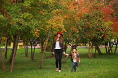 Mother and daughter walking holding hands at park. Family lifestyle concept. Stock Photo