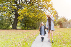 Mother and daughter walking holding hands at park Stock Photo