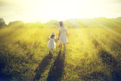 Mother and daughter walking on the meadow Royalty Free Stock Image
