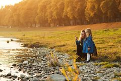 Mother and daughter walking near river in autumn time. Happy family. Fall weekend in the open air. Family enjoying beautiful autum. N nature. Autumn fashion stock photo
