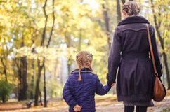 Mother with daughter walking in the park in autumn holding hands. Yellow leaves on tress. Back view Royalty Free Stock Images