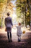 Mother with daughter walking in the park in autumn holding hands. Yellow leaves on tress. Back view Royalty Free Stock Photography