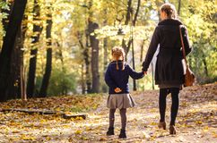 Mother with daughter walking in the park in autumn holding hands. Yellow leaves on tress. Back view Stock Image