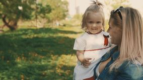 Mother and daughter walking in park, beautiful mom with little children outdoor stock video