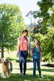 Mother and daughter walking in the park with dog Royalty Free Stock Photography