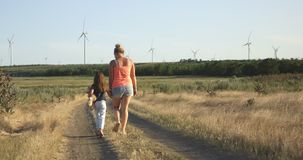 Mother and daughter walking on pathway
