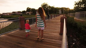 Mother and daughter walking on the pier at sunset. 4K stock footage