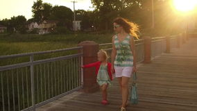 Mother and daughter walking on the pier at sunset. Slomotion stock video footage