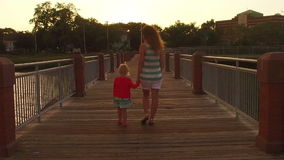 Mother and daughter walking on the pier at sunset. Slomotion stock footage