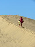 Mother and daughter walking on sand dune Stock Photo