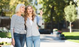 Mother and daughter walking, spending time together. In city park, copy space royalty free stock photos