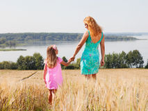 Mother and daughter walking  in summer field Royalty Free Stock Image