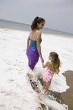 Mother and daughter walking through surf Royalty Free Stock Photography
