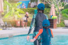 Mother and Daughter walking in a swimming pool royalty free stock photography