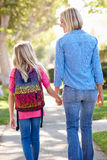 Mother And Daughter Walking To School On Suburban Street Stock Images