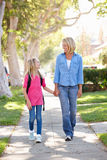 Mother And Daughter Walking To School On Suburban Street Royalty Free Stock Images