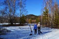 A mother and daughter walking in the winter snow. royalty free stock photo