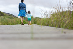Mother and daughter walking on wooden plank in nature Royalty Free Stock Images