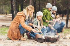 mother and daughter warming hands with bonfire while father and son royalty free stock photos