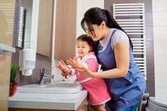 Mother and daughter washing their hands in the bathroom. Care an. D concern for children.Hygiene Stock Photo