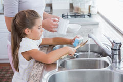 Mother and daughter washing up Stock Photography
