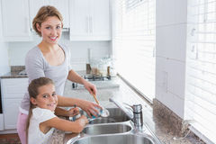Mother and daughter washing up Stock Images