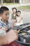 Mother and Daughter Watch as Father and Son Try to Fix the Car Stock Images