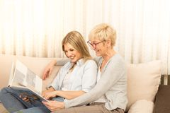 Mother and daughter watch family photo album. stock photos