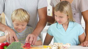 Mother and daughter watching father and son slicing vegetables Royalty Free Stock Photo