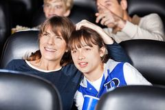 Mother And Daughter Watching Film In Theater Stock Photos