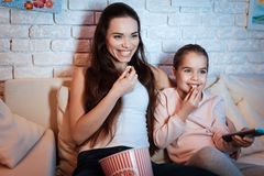 Mother and daughter watching movies on television at night at home. stock photos