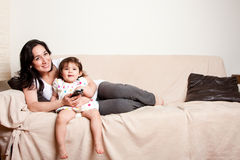Mother and daughter watching TV stock images