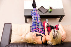Mother and daughter watching TV on the sofa Stock Photography