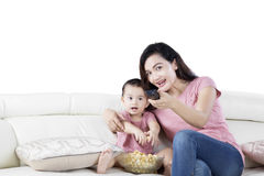 Mother and daughter watching tv on studio. Image of beautiful mother and daughter watching tv together while eating popcorn in the studio Stock Photos
