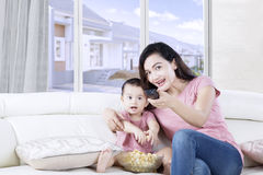 Mother and daughter watching TV together. Young Asian mother and daughter watching TV together while eating popcorn and sitting on the couch Royalty Free Stock Images