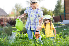Mother And daughter watering plants in garden Royalty Free Stock Photos